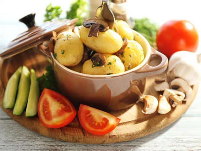 Young boiled potatoes in pan with vegetables on table in kitchen