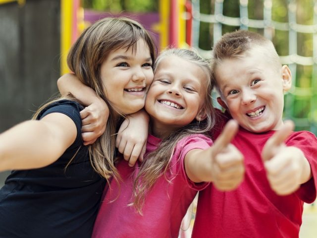 18184841 - happy children showing ok sign on playground