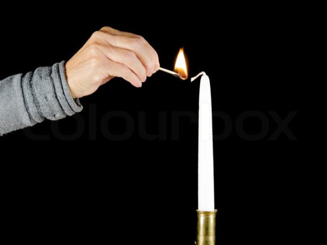 11639094-a-hand-with-a-burning-match-is-lighting-a-white-candle